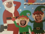 Shows Pat and two Zurich players grinning through a cut our of Santa and 2 Elves